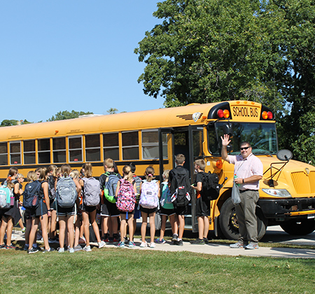 Principal and cross country team next to bus