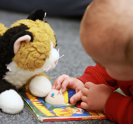 baby with book and toy cat