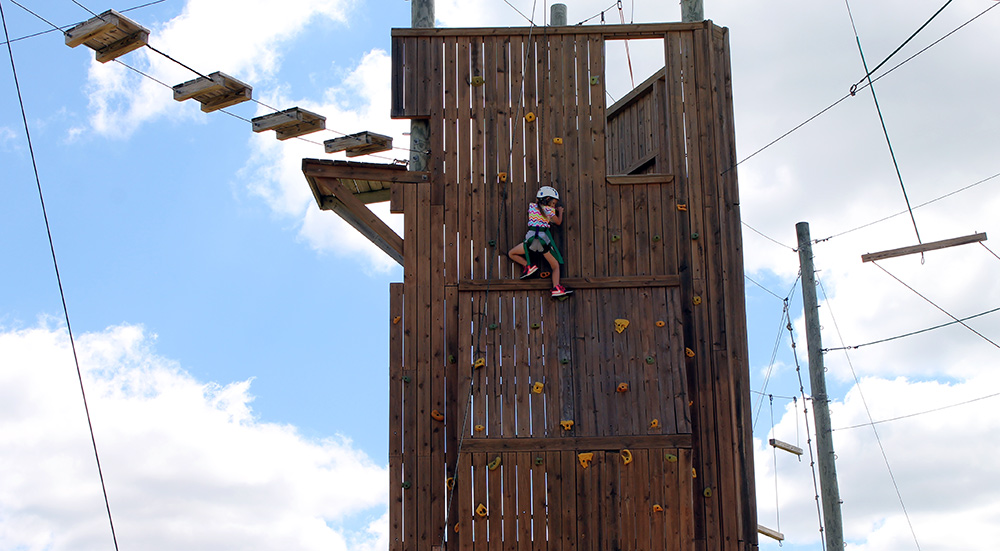 A student climbs the rock wall on the Adventure Ropes Course