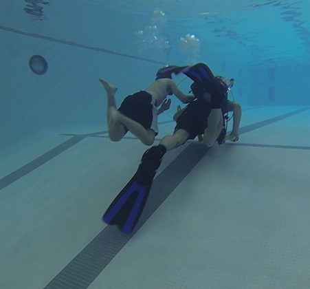 A student and a SCUBA instructor swim in the PHS pool
