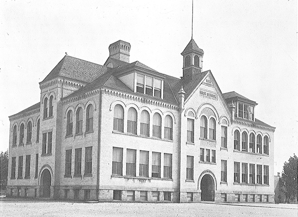 Cream-colored brick school with arched windows